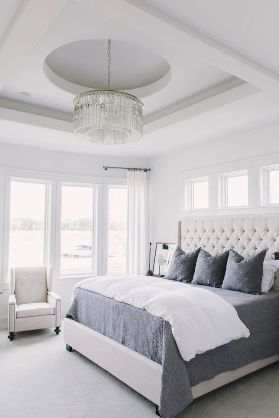 a creamy tufted headboard and a crystal chandelier are glam and cool accents for the space