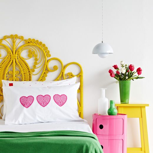 a creative woven yellow headboard matches the bright color scheme of the bedroom