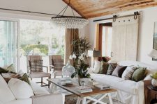 living room with a stylish wooden ceiling and a statement chandelier