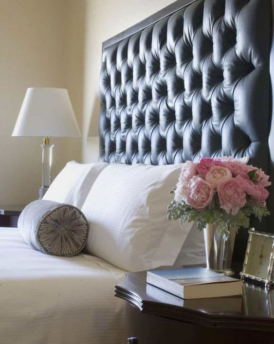 a super tall black tufted headboard with framing is a bold and dark statement in the neutral bedroom