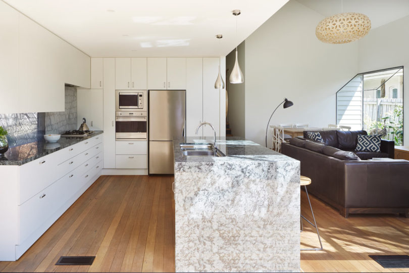 A large kitchen island with a grey stone countertop separates two zones from each other
