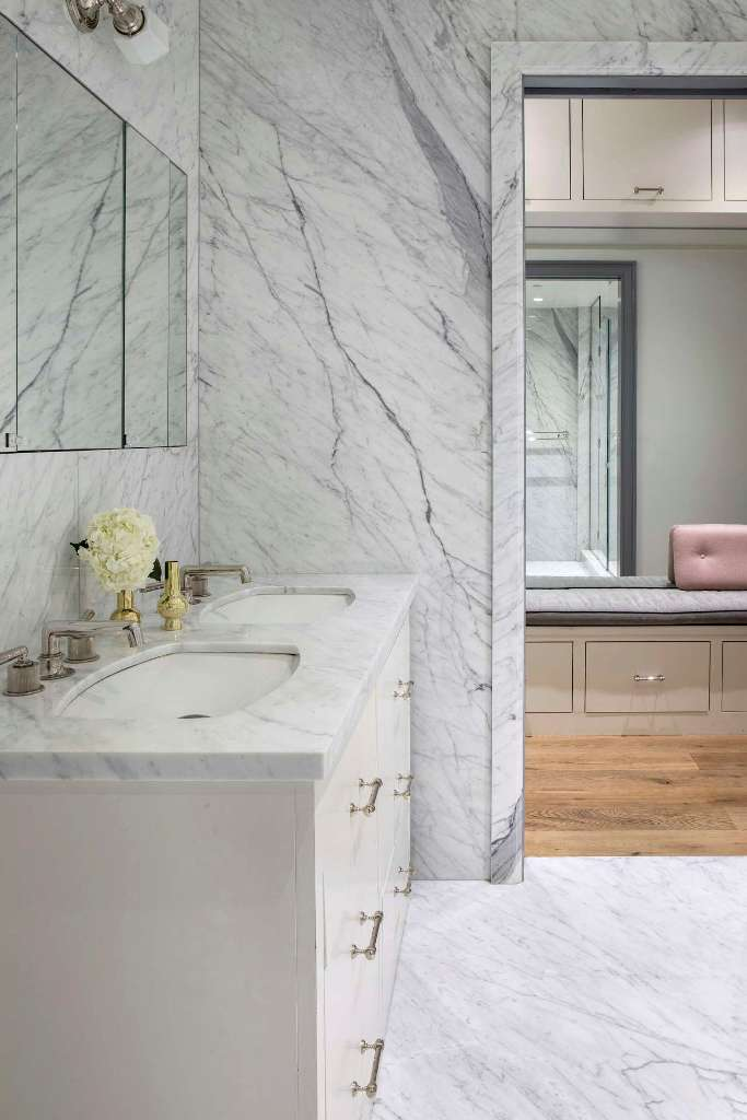 The bathroom is done with white marble, which adds a refined touch at once