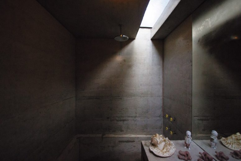 The bathroom is private and is made of concrete, with a skylight and some seashells for decor