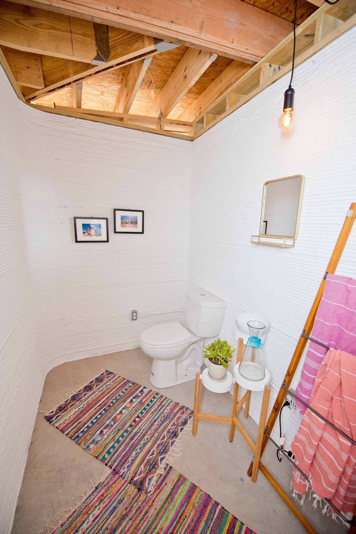 The bathroom is small and is done with simple stands, a ladder for towels and colorful rugs