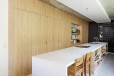 08 The kitchen is done with light-colored wooden cabinets, a large and long white kitchen island with an eating space