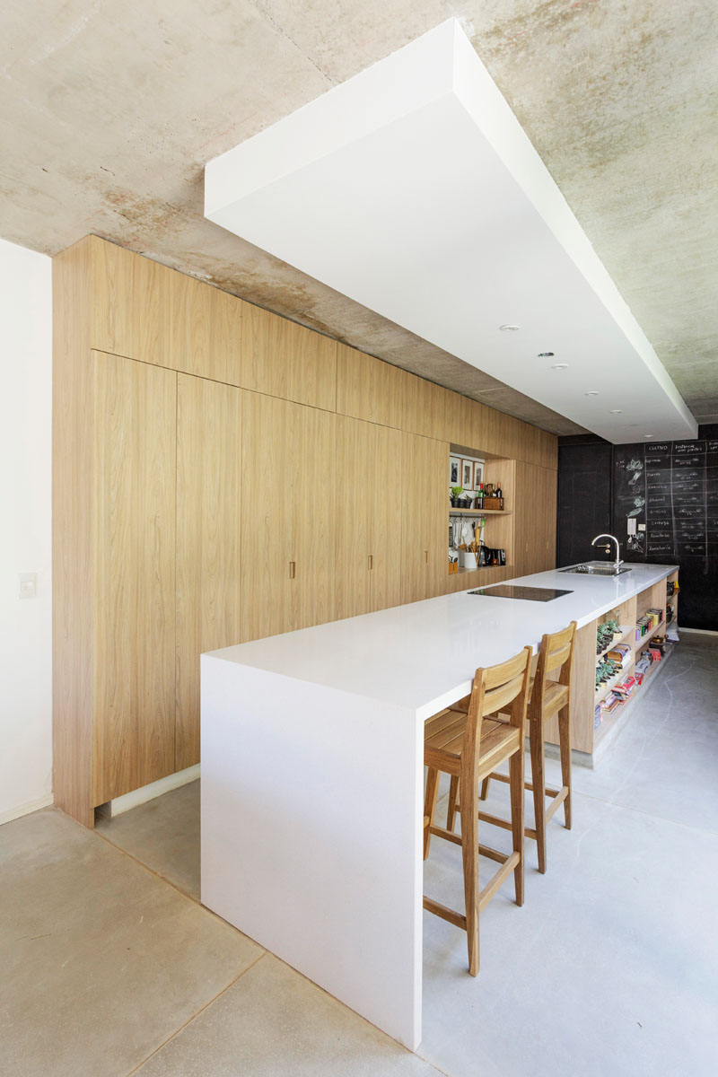 The kitchen is done with light colored wooden cabinets, a large and long white kitchen island with an eating space