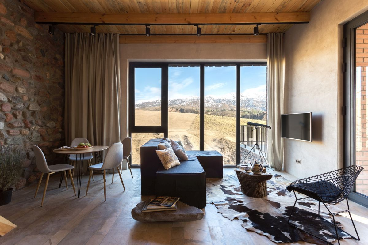The living and dining space feature amazing views, an animal skin rug, contemporary furniture