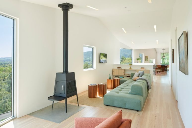 The living room features a chic green sofa and a hearth and I also love tree stump tables