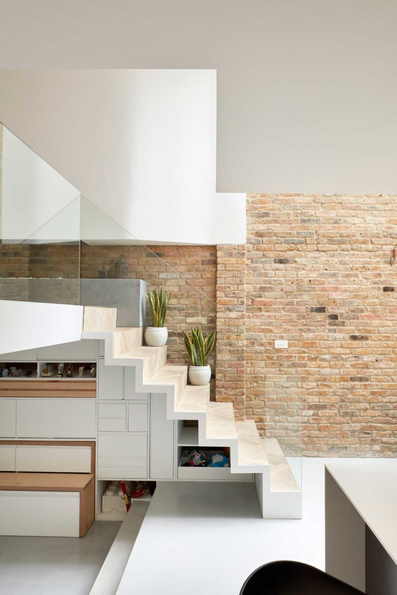 The staircase is ultra minimalist and very sleek, with hidden storage and glass railing