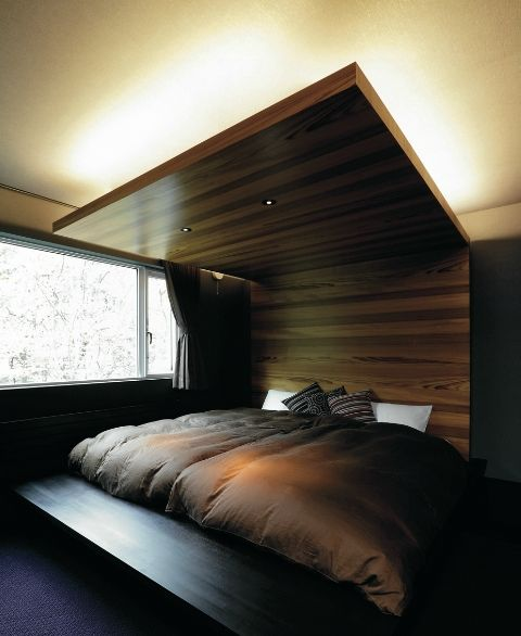 a gorgeous wooden headboard extended up to the ceiling features lights and creates a cozy sleeping alcove