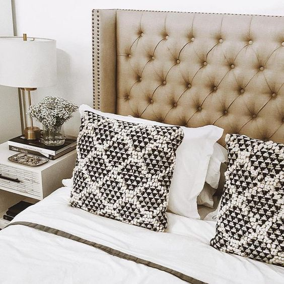 a neutral tufted wingback headboard with decorative nail trim is a chic and timeless idea that never goes out of style