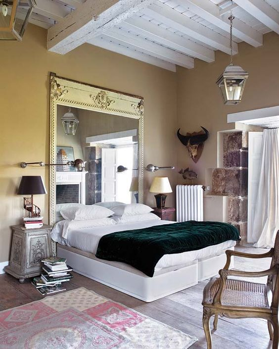 a statement mirror in a vintage frame is a unique headboard idea for a beautiful bedroom