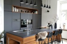 08 a super chic dark kitchen with matching blakc pendant lamps hanging in a row is a cool and bold idea