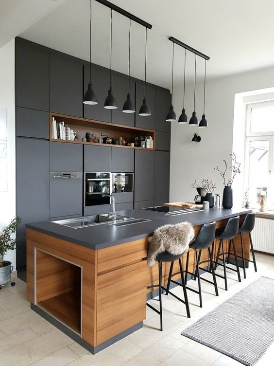 a super chic dark kitchen with matching blakc pendant lamps hanging in a row is a cool and bold idea