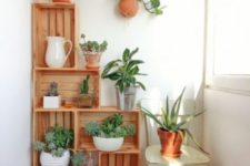 08 a wooden crate shelving unit acts as a garden with potted greenery, a great idea for decorating a small balcony