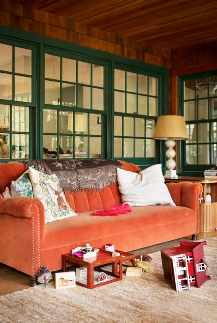 an orange velvet sofa brings traditional fall chic to this screened porch and makes it feel like fall