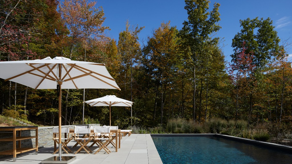 The outdoor space is done with a vast terrace, an outdoor dining space and a large pool