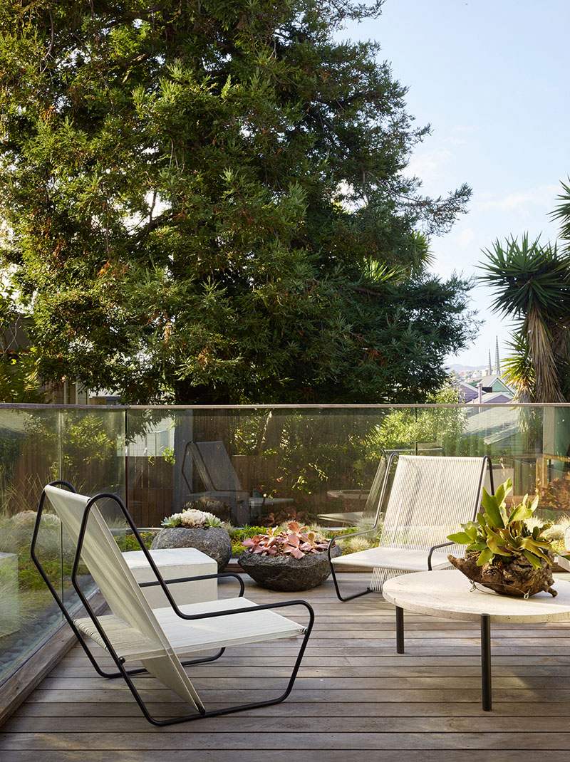 The terrace is laconic and simple and features amazing modern chairs