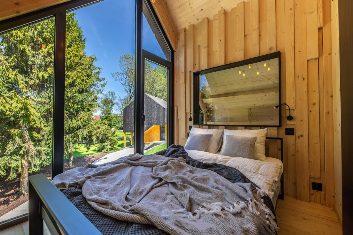 The walls, floor and ceiling of the bedroom are covered in wood and that creates a very cozy and inviting ambiance