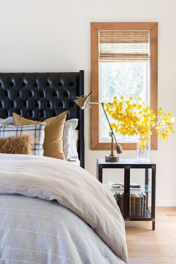 a black leather wingback tufted headboard and a dark stained nightstand add drama to the neutral bedroom