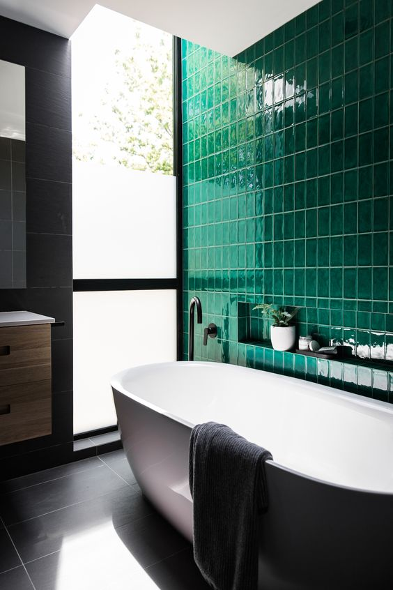 a contemporary bathroom done with a statement wall of emerald tiles and calm grey tiles on the rest of the surfaces