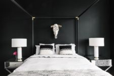 09 a gorgeous bedroom with black walls, a framed bed, mirror nightstands and a skull on the wall