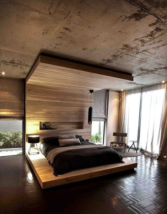 a platform bed extended to the wall and ceiling with a niche and a pendant lamp is an ultra-modern idea