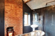 09 a stunning contrasting bathroom with a statement crystal chandelier, a metal tub and a brick wall with a hearth