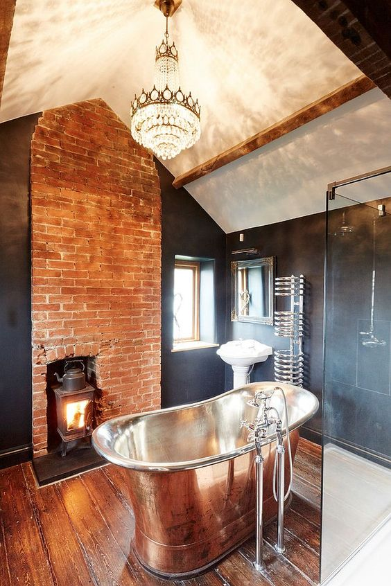 a stunning contrasting bathroom with a statement crystal chandelier, a metal tub and a brick wall with a hearth