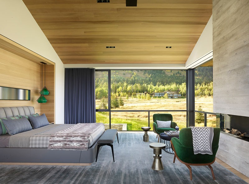 The bedroom features a fireplace and great views of the surroundings to enjoy fresh air