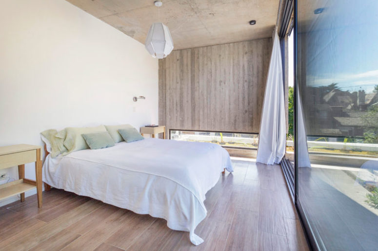 The bedroom is done with a glazed wall, a wooden wall with a small low skylight to make it more private
