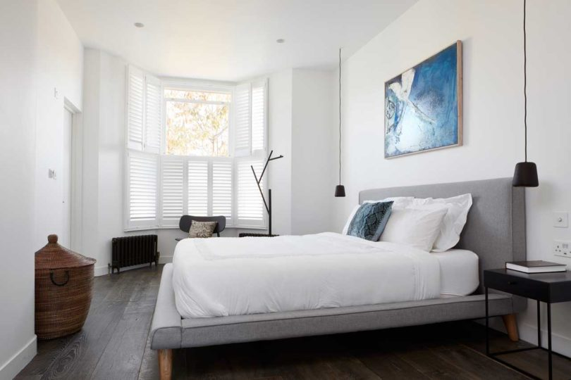 The master bedroom resembles the living room, there's a comfy upholstered bed, a shuttered window and a statement artwork