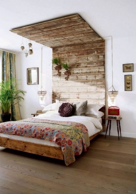 a weathered and aged wood headboard that is extended to the ceiling to have a bigger impact