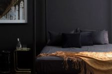 10 an elegant and moody bedroom with black walls, a framed bed and a statement artwork looks very relaxing