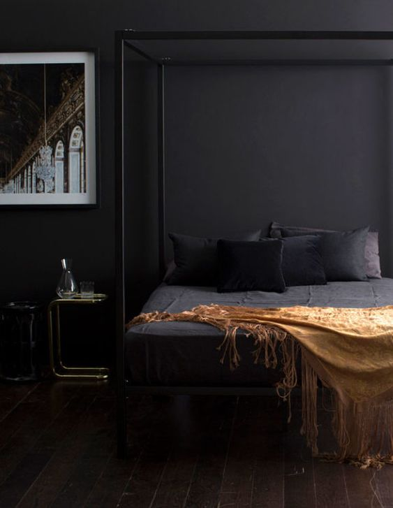 an elegant and moody bedroom with black walls, a framed bed and a statement artwork looks very relaxing