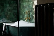 10 an exquisite dark green clawfoot bathtub surrounded with glossy green tiles on the walls
