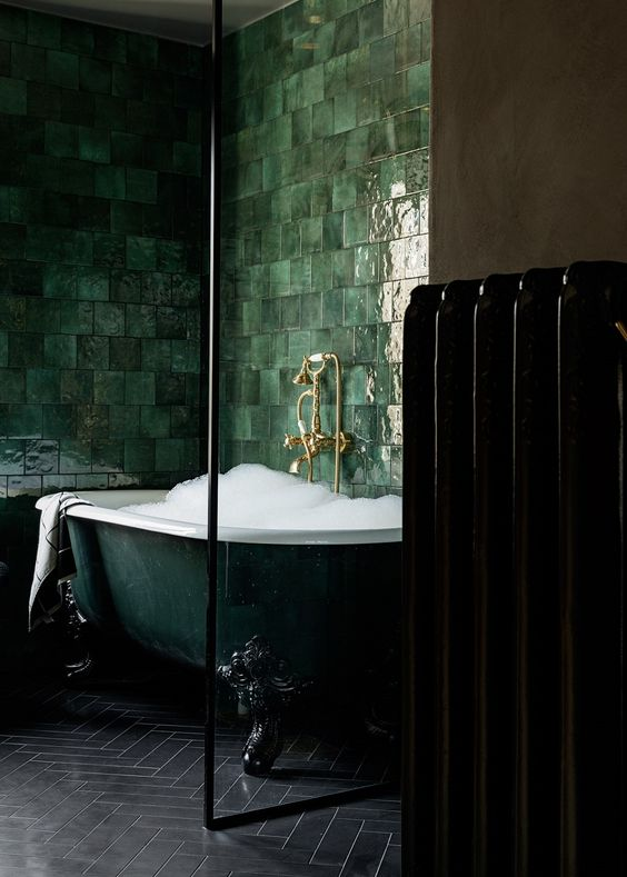 an exquisite dark green clawfoot bathtub surrounded with glossy green tiles on the walls