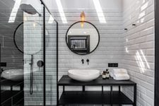 11 The bathroom is done with white subway tiles and black elements for a bold contrasting look