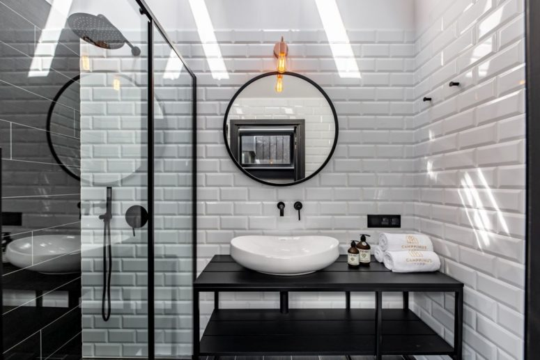 The bathroom is done with white subway tiles and black elements for a bold contrasting look