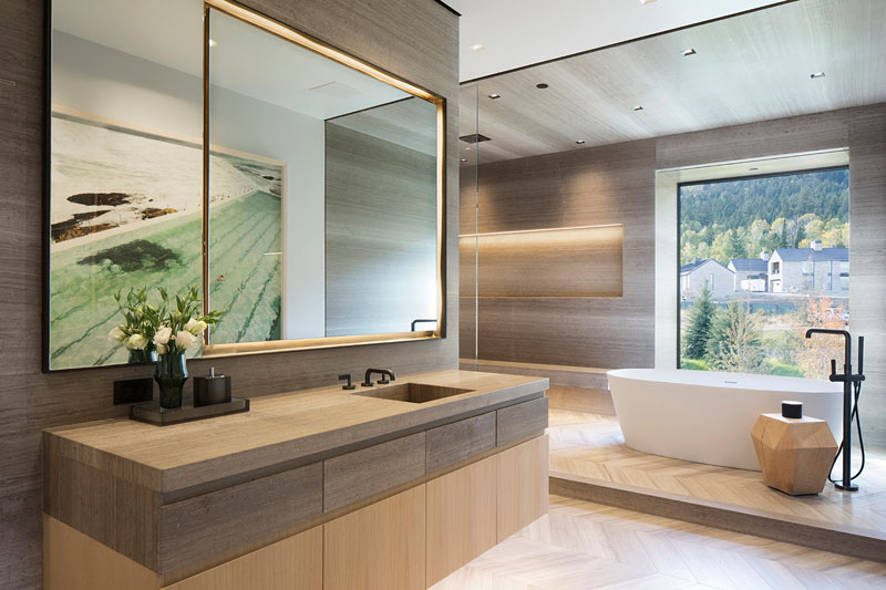 The contemporary bathroom is done with wood and a cool tub in front of the window