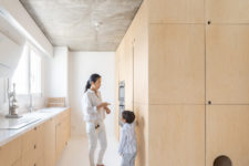 11 The kitchen is done with sleek plywood cabinets, a neutral countertop and some built-ins