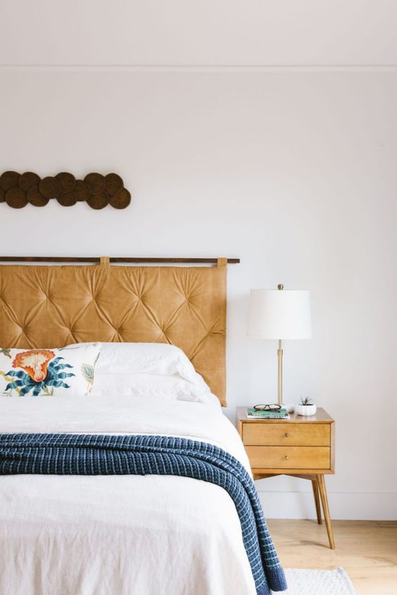 a hanging amber tufted leather headboard achoes with the nightstand and adds a warming up feel to the space
