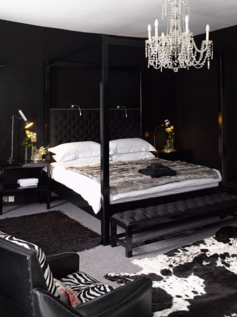 a luxurious bedroom with black walls, a crystal chnadelier, animal prints and some lights over the bed