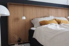 11 a sleek wooden headboard on a black wall makes a cozy and soothing statement and adds a calmign feeling to the room