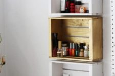 11 a trio of crate shelves on the wall in different colors to organize small stuff in your bathroom