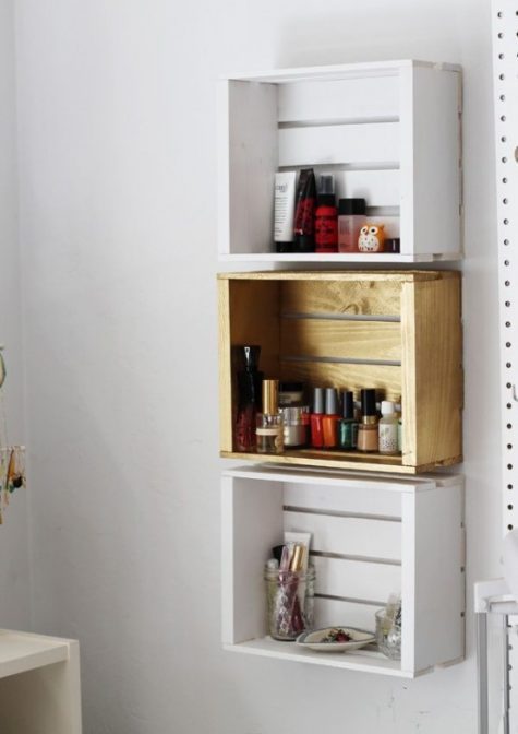 a trio of crate shelves on the wall in different colors to organize small stuff in your bathroom