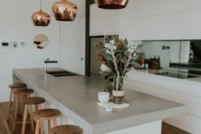 11 copper pendant lamps add a metallic touch and make the kitchen look bold, chic and catchy