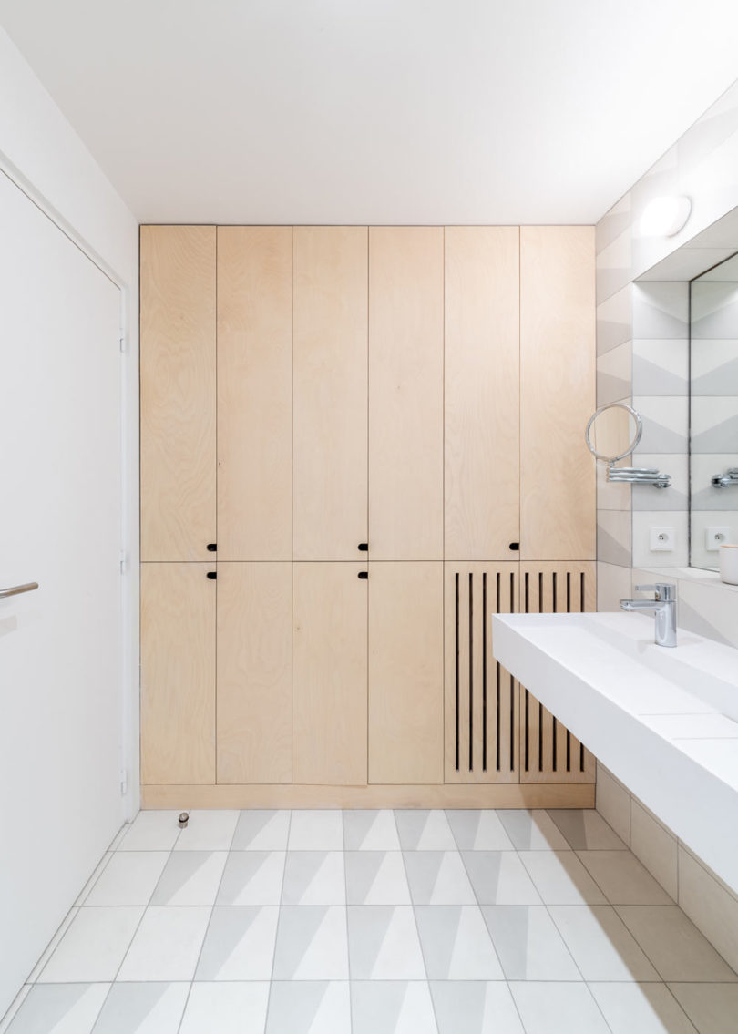 The bathroom continues the decor of the apartment with sleek plywood cabinets and neutral tiles