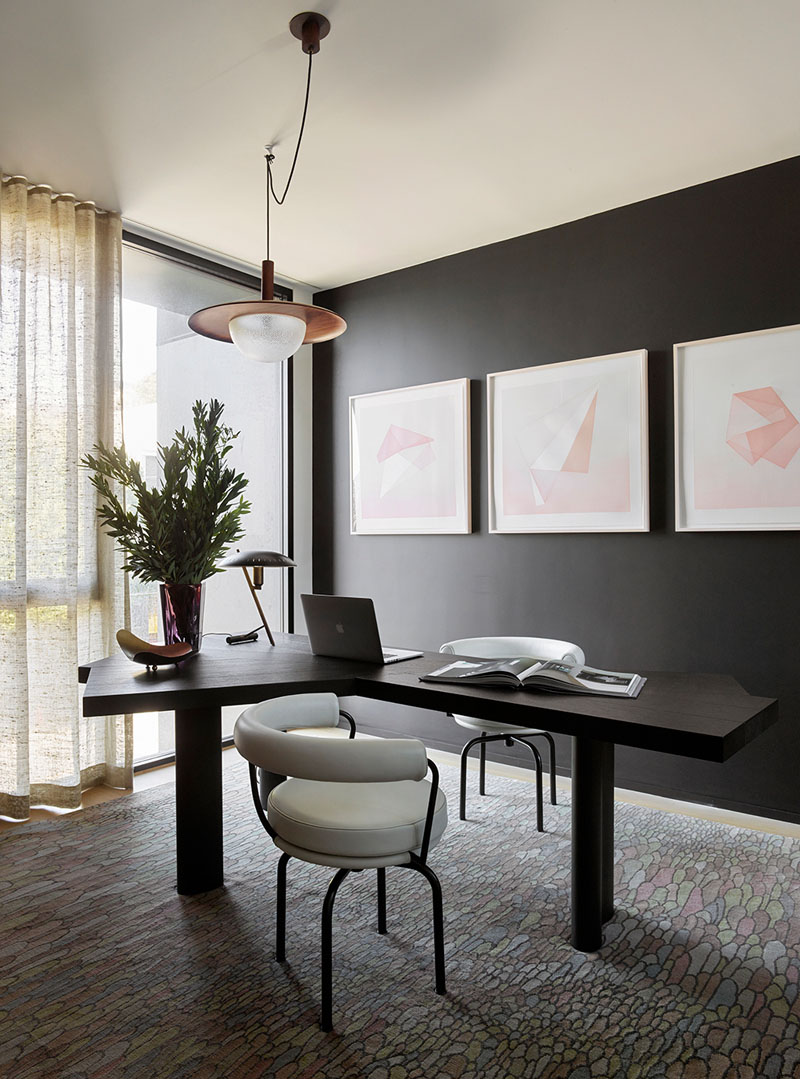 The home office nook is moody and is refreshed with pink artworks