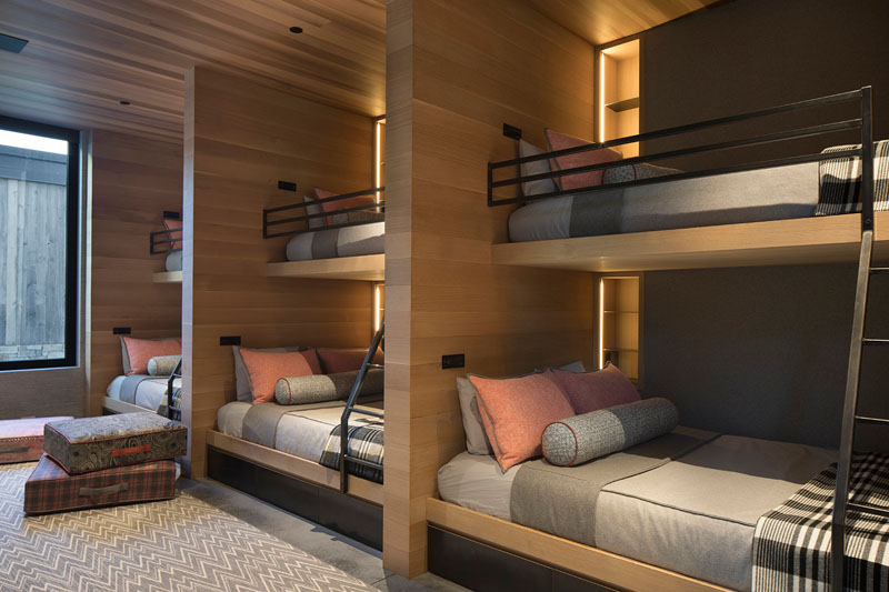 This is a multiple guest bedroom with lots of bunk beds and built in lights